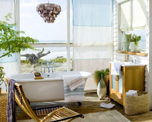 Light bright and airy beachside conservatory bathroom freestanding roll top bath with large floor to ceiling widows sea and beach view sheer curtain panel blind vanity wash basin sink cabinet jute fishing nets unusual light shade folding wooden chair rug CH&I 08/2008 pub orig